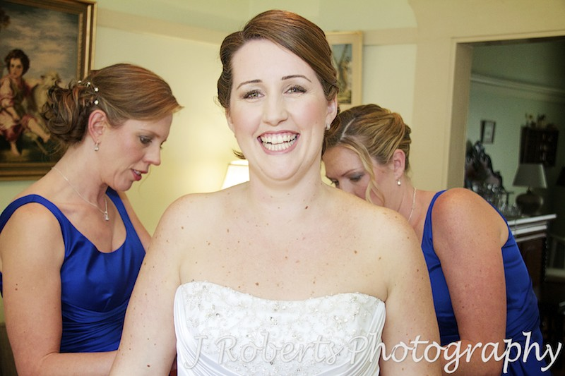 Bride having dress done up - wedding photography sydney