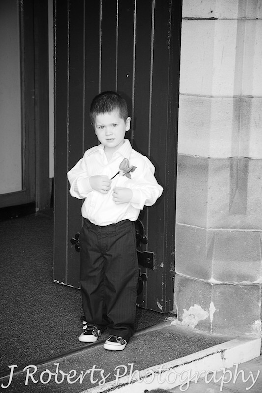 B&W of paige boy at church door - wedding photography sydney