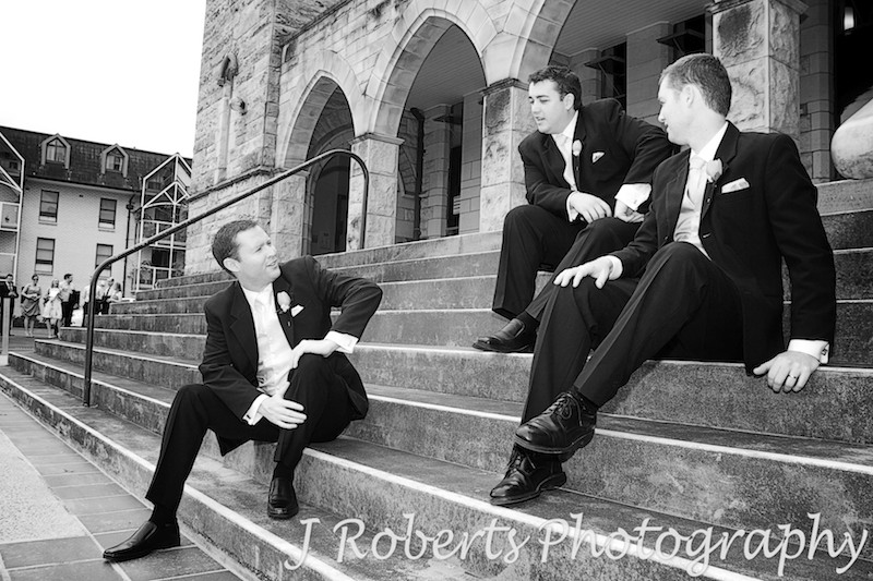 Groom sitting on St Francis Xavier Lavender Bay church steps - wedding photography sydney