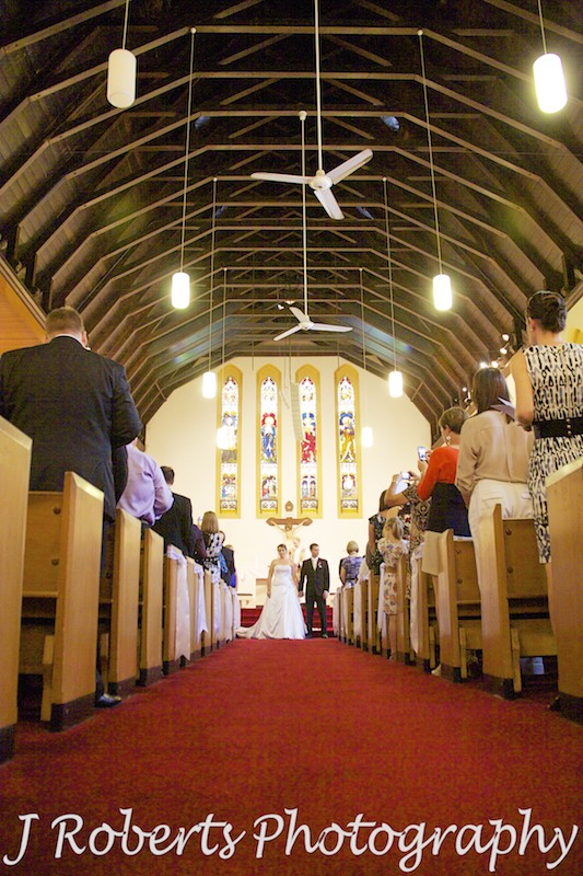 Looking down the aisle of St Francis Xavier Church Lavender Bay - wedding photography sydney