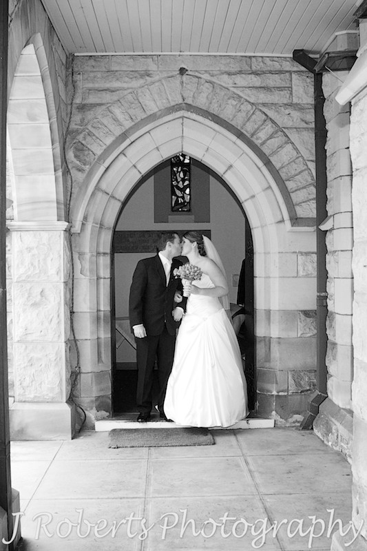 Bride and groom kissing on church steps - wedding photography sydney