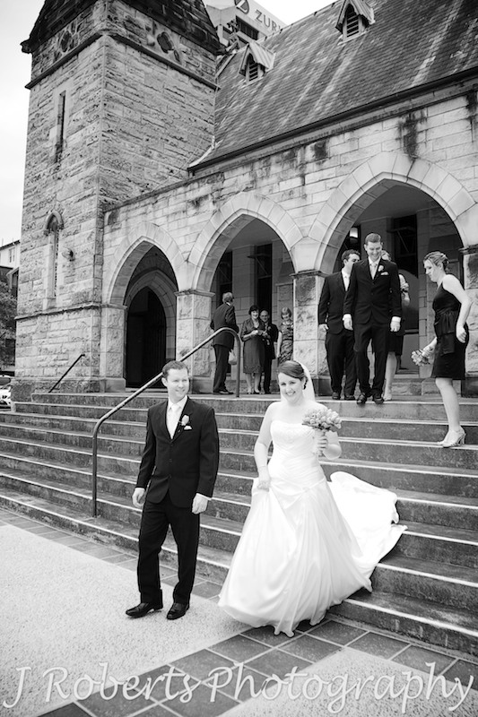 Bride and groom leaving the church followed by bridal party - wedding photography sydney