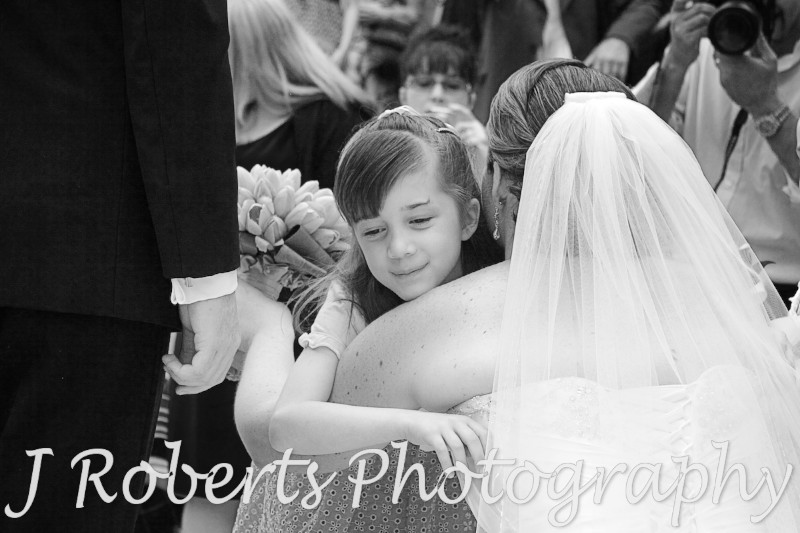 Flower girl hugging bride -wedding photography sydney