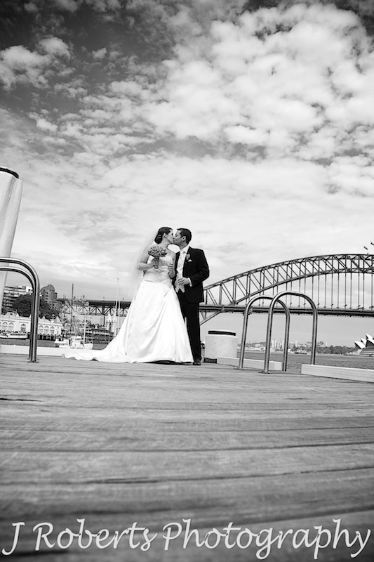 B&W bride and groom kissing on pier sydney harbour - wedding photography sydney
