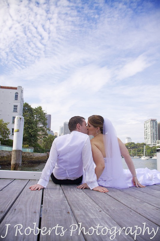 Bride and groom sitting on pier kissing - wedding photography sydney