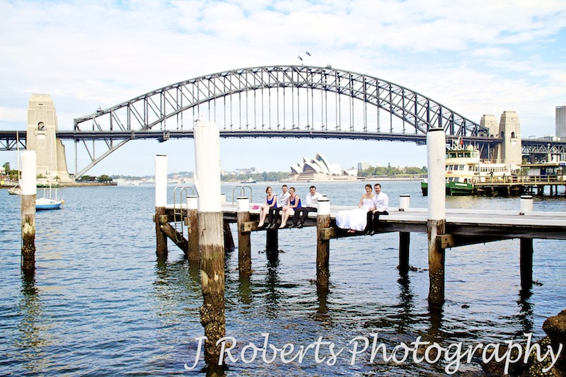 Bridal party sitting on edge of pier with Sydney Harbour Bridge, Opera House and ferry in the background - wedding photography sydney