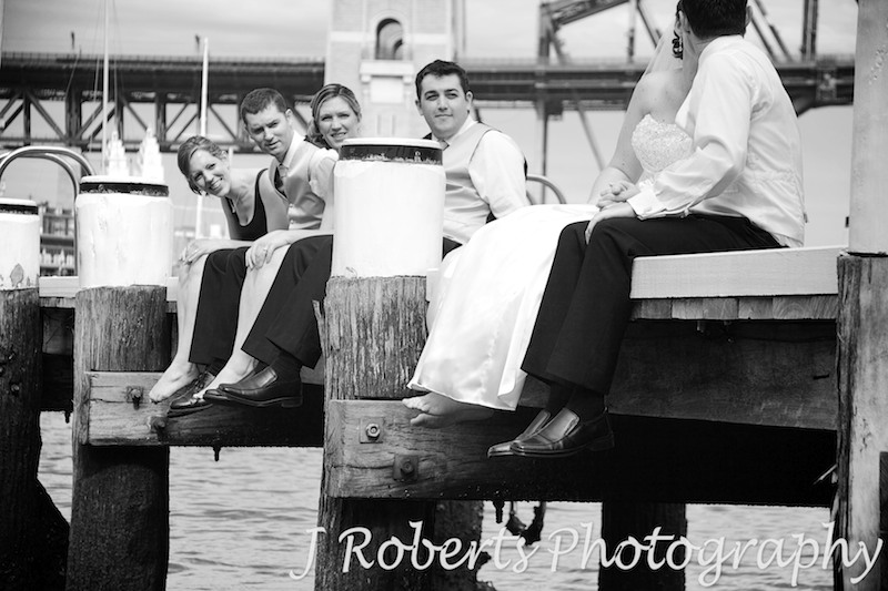 Bridal party looking at couple kissing on pier - wedding photography sydney