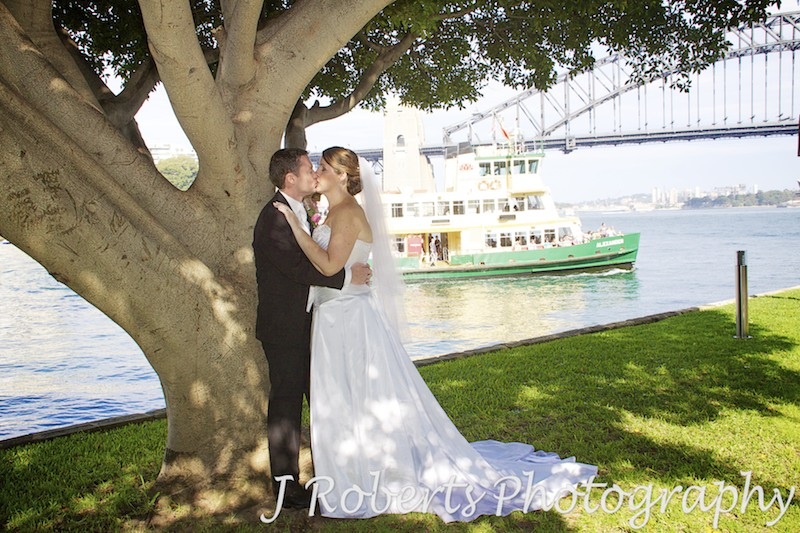 Bride and groom kissing under a tree with Sydney Ferry in the background - wedding photography sydney