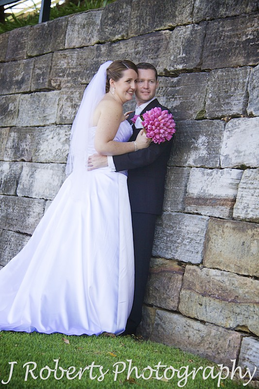 Bride and groom leaning against sandstone wall at Blues Point - wedding photography sydney