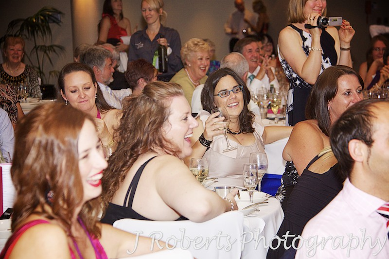 Guests laughing during speeches at wedding reception - wedding photography sydney