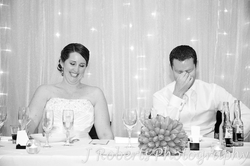 Bride and groom laughing during speeches at wedding reception - wedding photography sydney