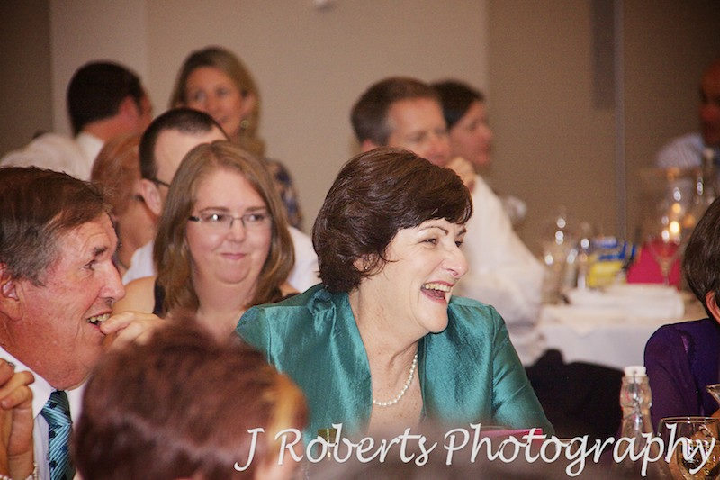 Mother of the bride laughing at speeches during wedding reception - wedding photography sydney