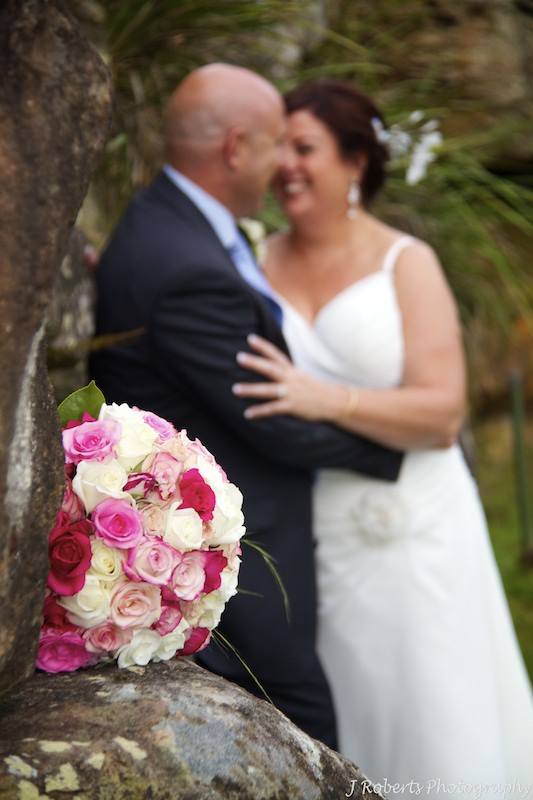 Bridal bouquet with couple behind by Show Posies - wedding photography sydney