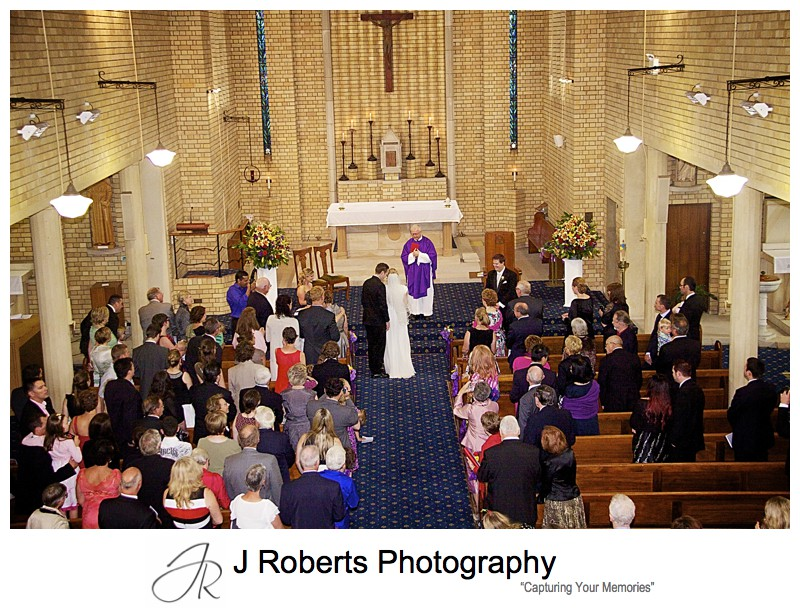 Groom whispering to bride when he sees her at the church - wedding photography sydney