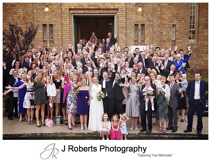 Whole group photo cheering after wedding ceremony - wedding photography sydney