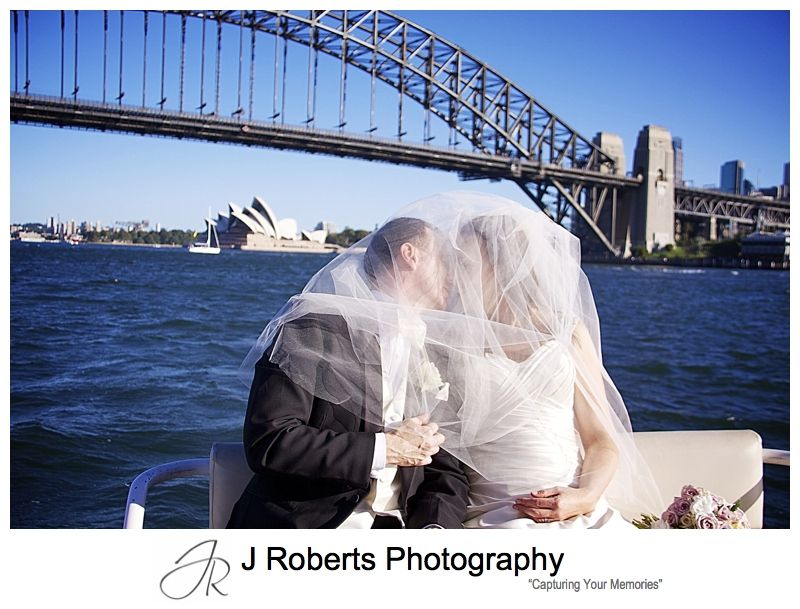 Couple kissing under a veil while riding a sydney water taxi - wedding photography sydney