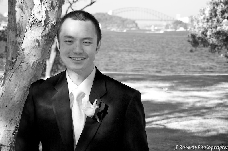 B&W of groom with sydney harbour behind - wedding photography sydney