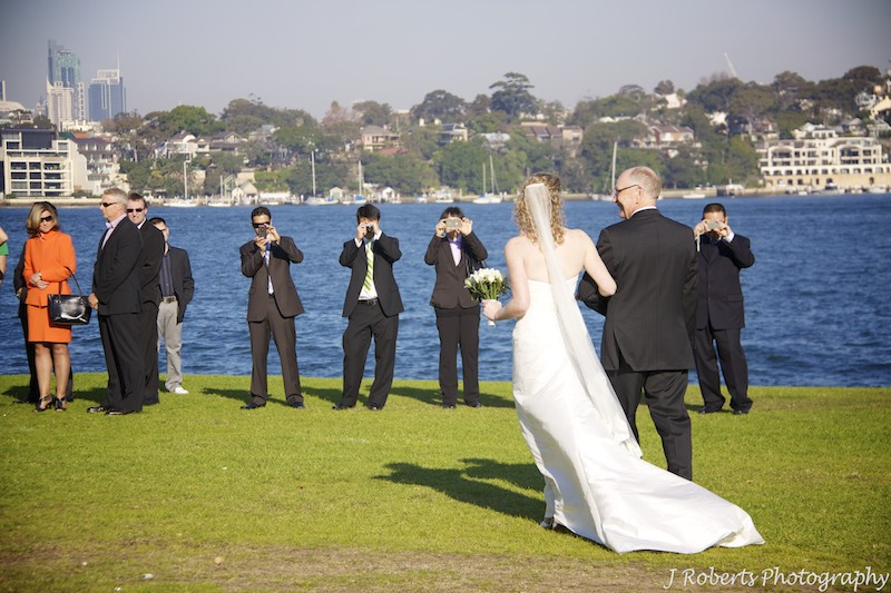 Bride and father walking down the aisle to guests with cameras - wedding photography sydney