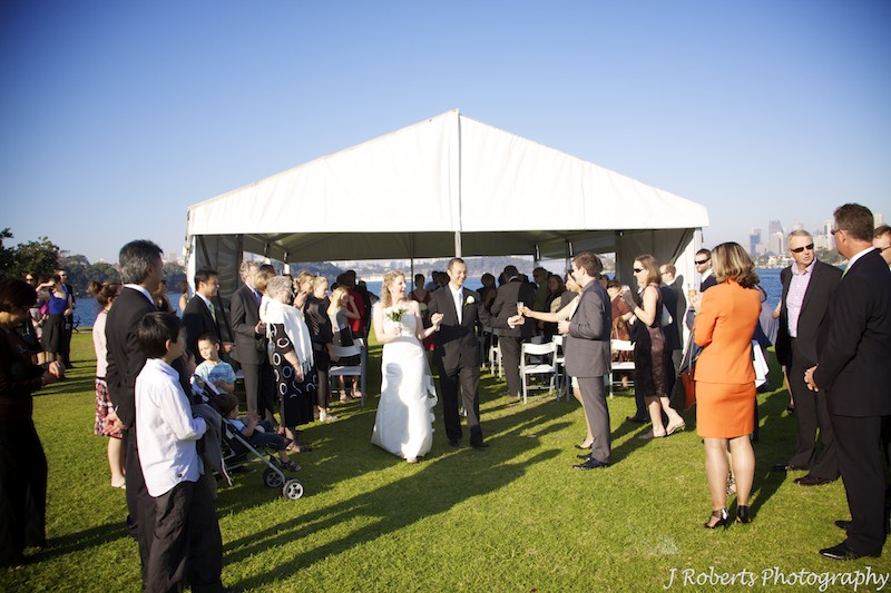 Bride and groom exiting the marquee after wedding ceremony - wedding photography sydney