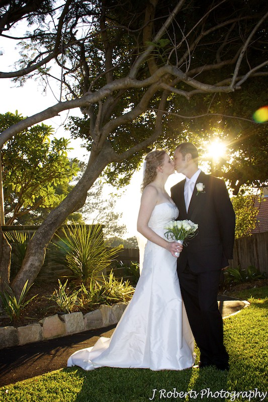 Kissing couple with setting sun - wedding photography sydney