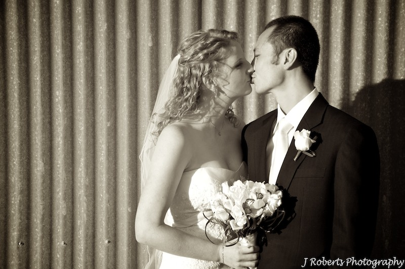 Sepia kissing couple with corrugated iron wall behind - wedding photogrpahy sydney