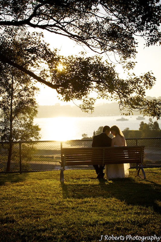 Couple sitting on bench looking at setting sun - wedding photography sydney