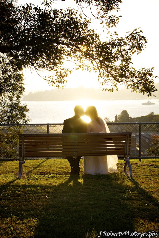 Couple sitting on bench kissing with setting sun behind - wedding photography sydney