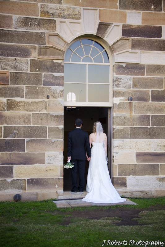 Bridal couple walking through a doorway - wedding photography sydney